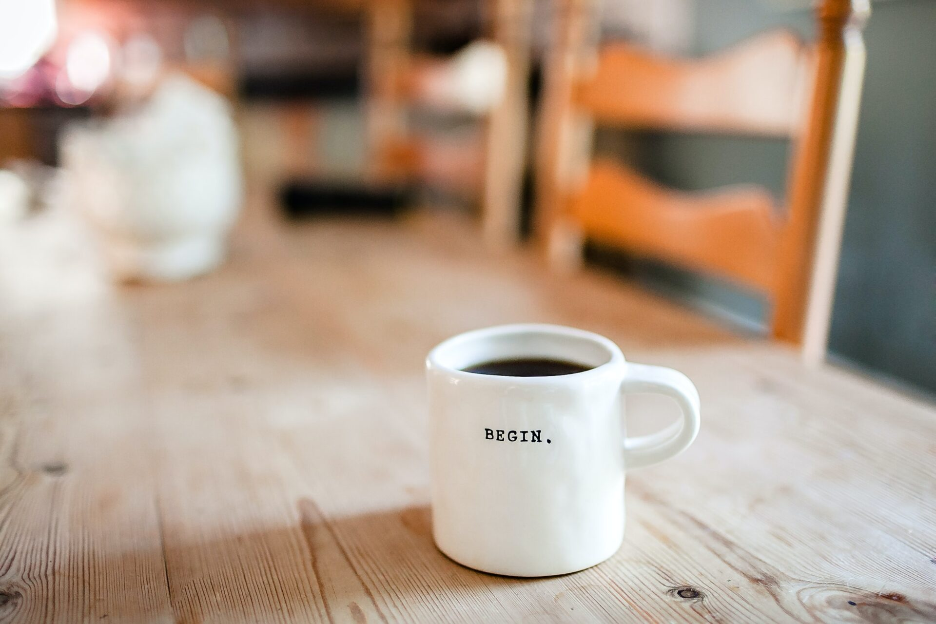 Coffee cup with the word begin written on it sitting on a wooden table