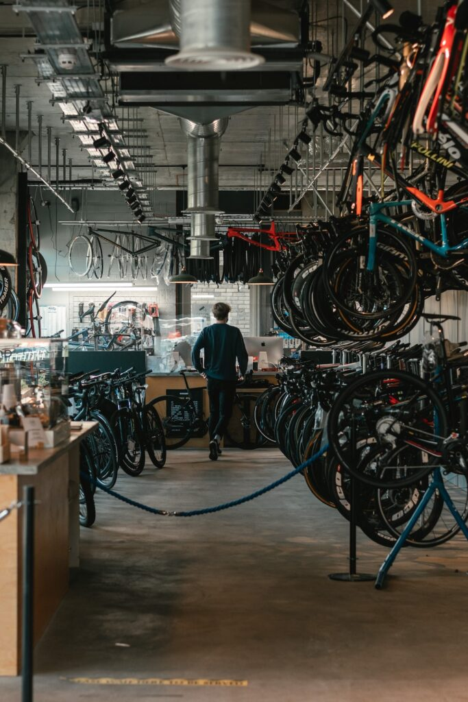 A bicycle store with mountain bikes hanging from wall racking and a servicing area with equipment obtained via an equipment loan in the background.
