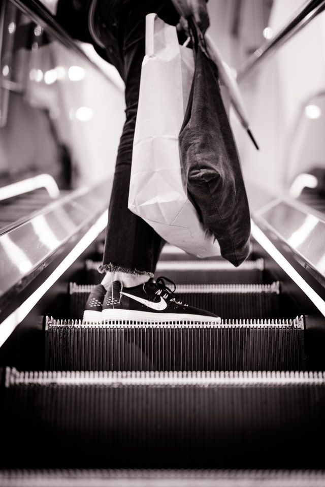 black and white photo of person on an escalator with shopping bags during a post-pandemic business boom
