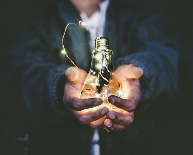Man in business suit holding glowering light bulb as a metaphor for business growth strategies