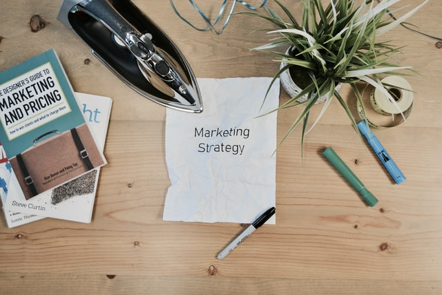 Desk with some marketing text books, a plant, three pens, and a piece of paper that says 'marketing strategy' with an iron over the top left of the crinkled page to symbolise ironing out the creases in a marketing strategy that aligns with your financial goals.