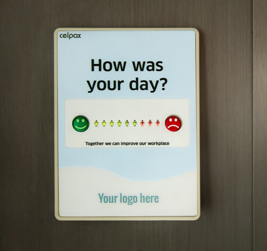 """Feedback board on the wall of a workplace that asks employees """"How was your day?"""" and lets them tap a green happy face through to a red sad face to gauge and reduce staff turnover"""